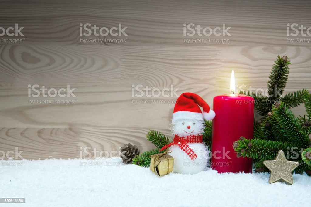 Avent candle and Christmas snowman isolated on wood background....