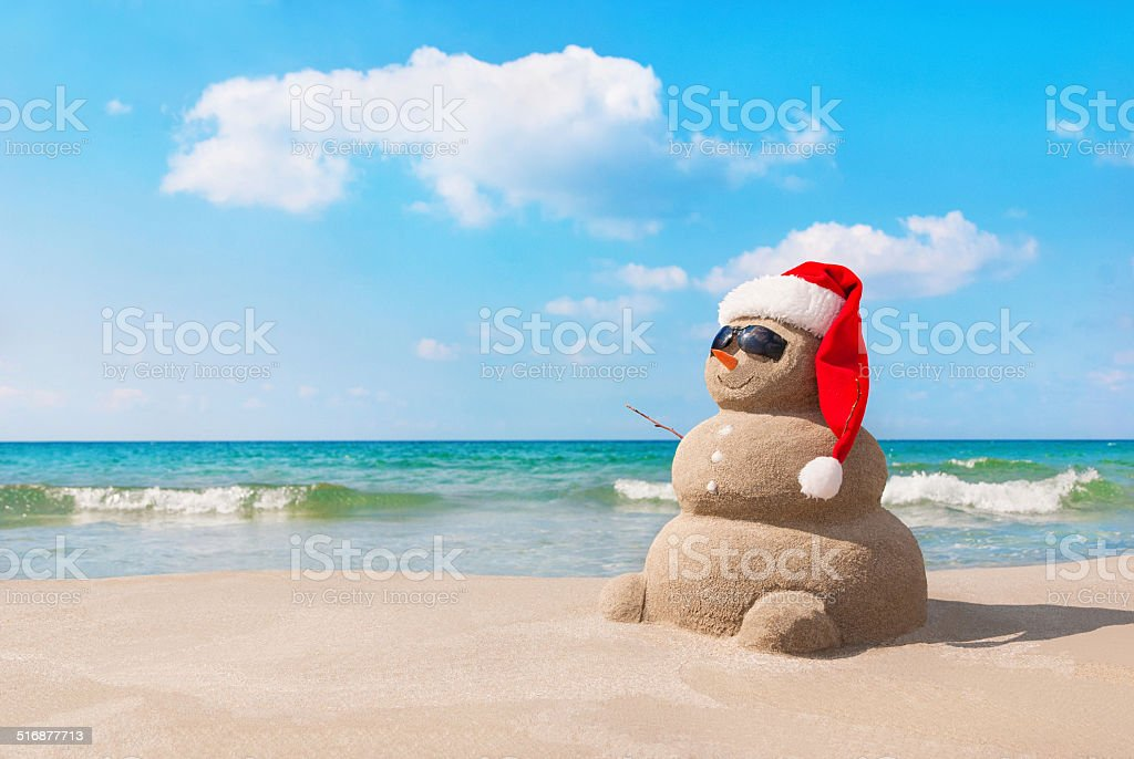Christmas snowman in santa hat at sandy beach stock photo