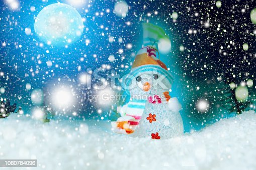 865140324 istock photo Christmas snowman with Xmas lights and snow on moonlights. The elements of this image furnished by NASA 1060784096