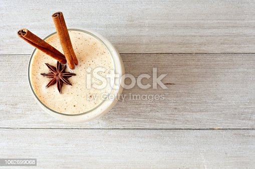 istock Christmas spiced eggnog in a glass, top view on gray wood 1062699068