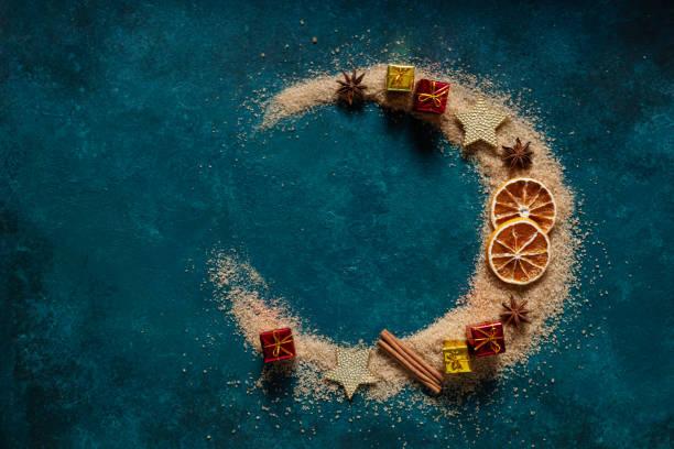 As especiarias e a decoração do Natal, açúcar marrom derramaram a meia forma da lua no fundo azul - foto de acervo