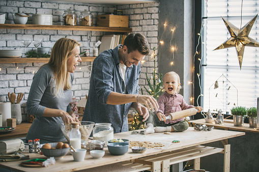 Family with one child making some cookies for Christmas holidays