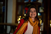 Lovely young woman on the street surrounded with Christmas decoration is smiling an enjoy the holiday.