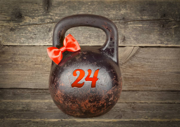 Christmas sport concept Red bow on Kettlebell Red bow on Old rusty Kettlebell over wooden table number 24 Christmas sport concept boss's day stock pictures, royalty-free photos & images