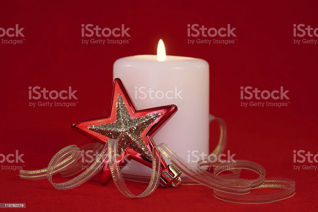 Christmas star bauble and white candle isolated on red royalty-free stock photo