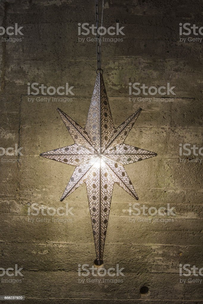 Christmas star in front of concrete wall stock photo