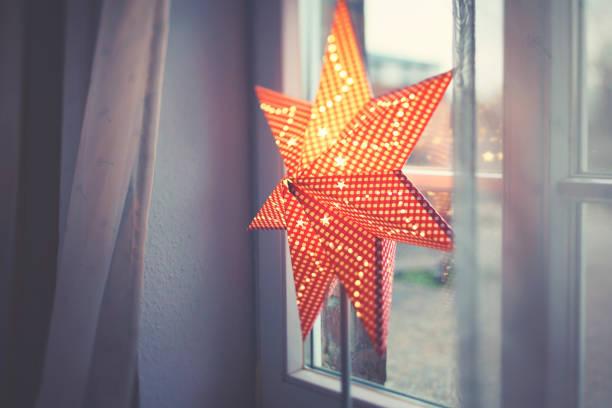 weihnachtssternlampe auf der fensterbank - weihnachtssterne aus papier stock-fotos und bilder