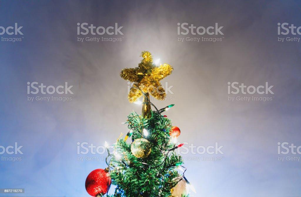 Luzes de Natal estrela na árvore de Natal com enfeites e colorido sobre fundo azul suave - foto de acervo