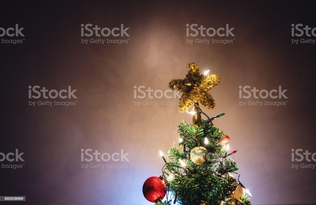Estrela de Natal na árvore de Natal com enfeites e luzes coloridas - foto de acervo