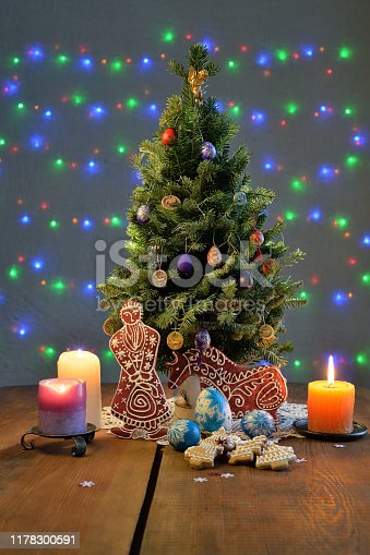 Christmas tree with the gingerbread Santa and horse, candles, ornate eggs on the table