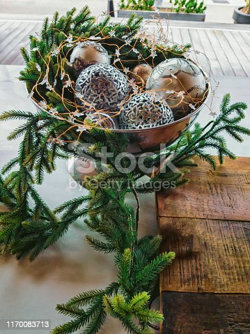 Christmas still life. Vase with Christmas balls and pine branches.
