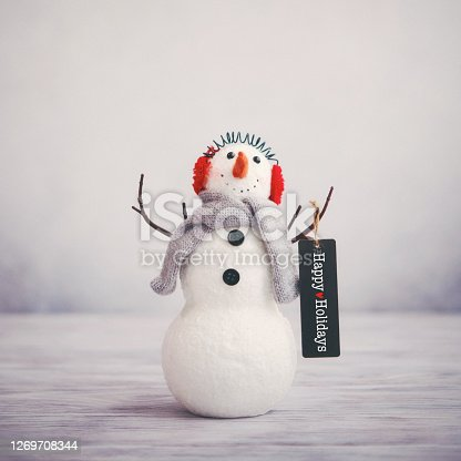 Christmas still life with cute snowman holding happy holidays greeting