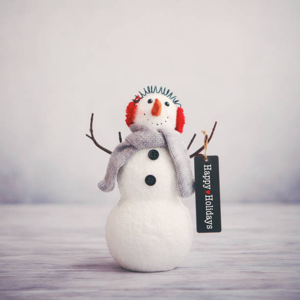 Christmas still life with cute snowman holding happy holidays greeting stock photo