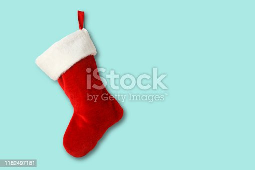 A red and white Christmas stocking isolated on a blue background that provides ample room for copy and text.