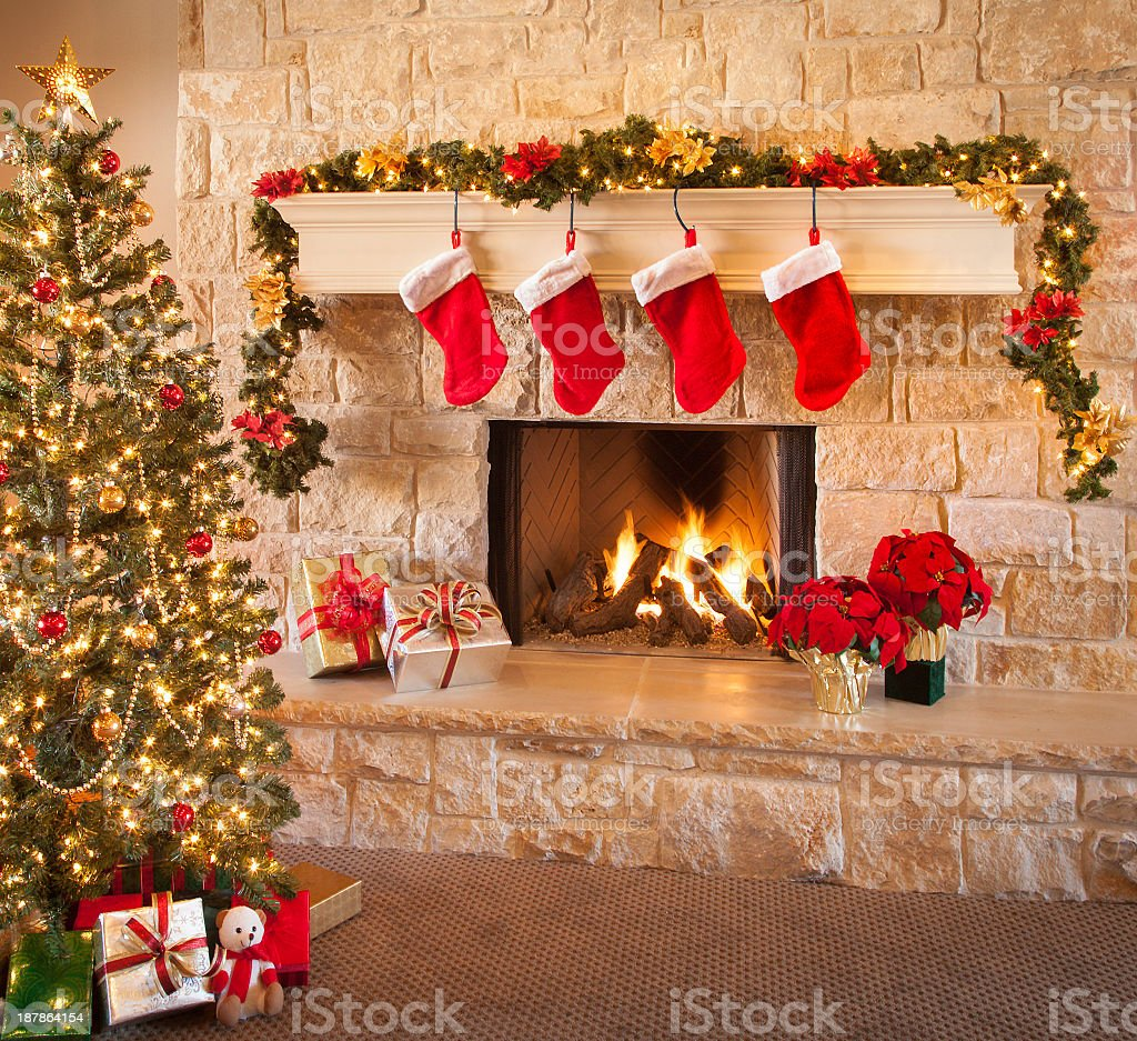 Christmas stockings, fire in fireplace, tree, and decorations stock photo