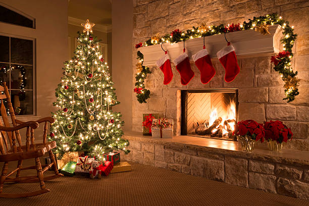 Christmas stockings, fireplace, tree, and decorations stock photo