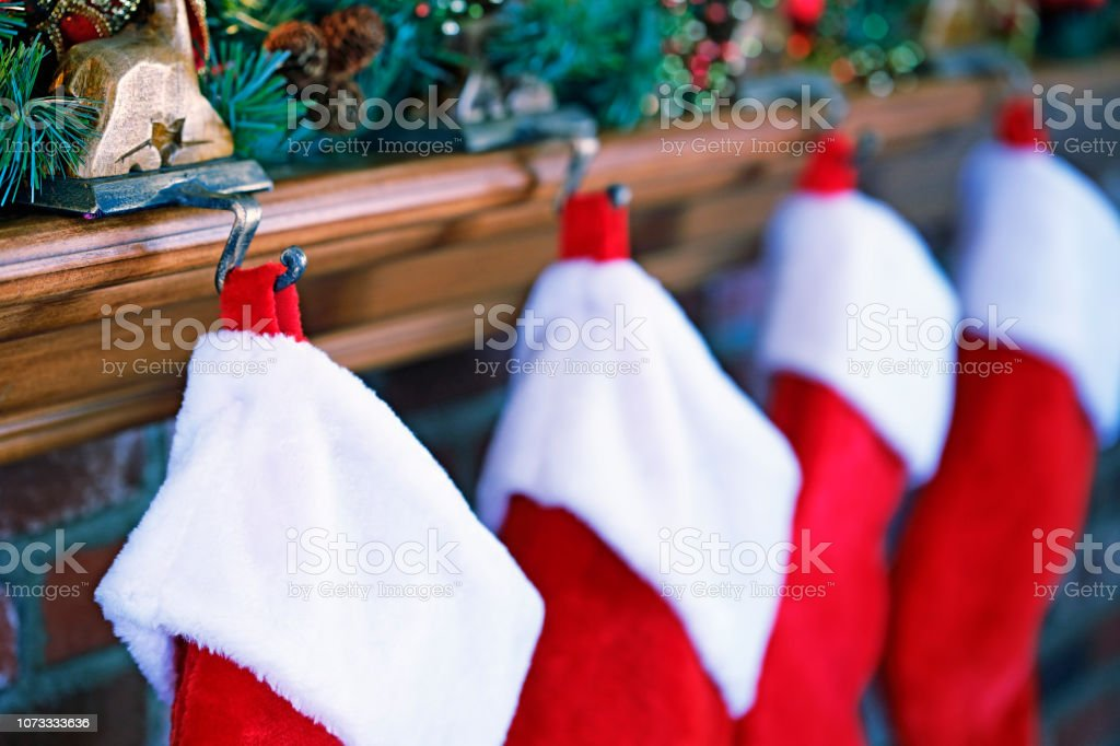 Christmas Stockings Hanging From Mantelpiece stock photo