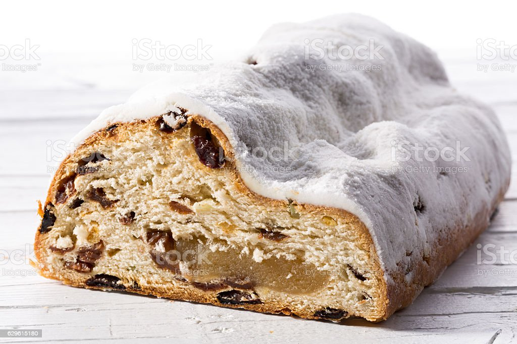 Christmas stollen cutted on white wooden background stock photo