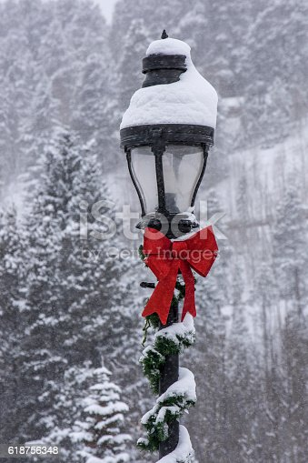 A lamp post decorated for Christmas and covered in snow