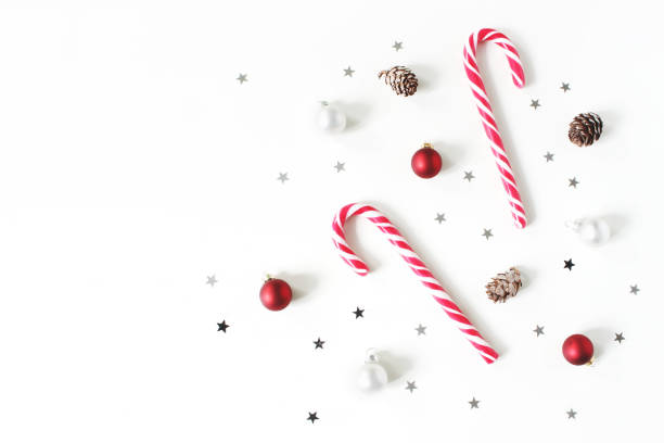 Christmas styled composition. Christmas red and white balls, baubles, candy canes, glittering silver stars confetti decoration and larch cones on white background. Flat lay, top view. Winter patttern. Christmas styled composition. Christmas red and white balls, baubles, candy canes, glittering silver stars confetti decoration and larch cones on white background, flat lay, top view. Winter patttern. candy cane stock pictures, royalty-free photos & images