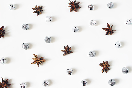 istock Christmas styled stock composition. Glittering silver jingle bells and anise stars on white background. Flat lay, top view. Winter decorative pattern. 1076899810