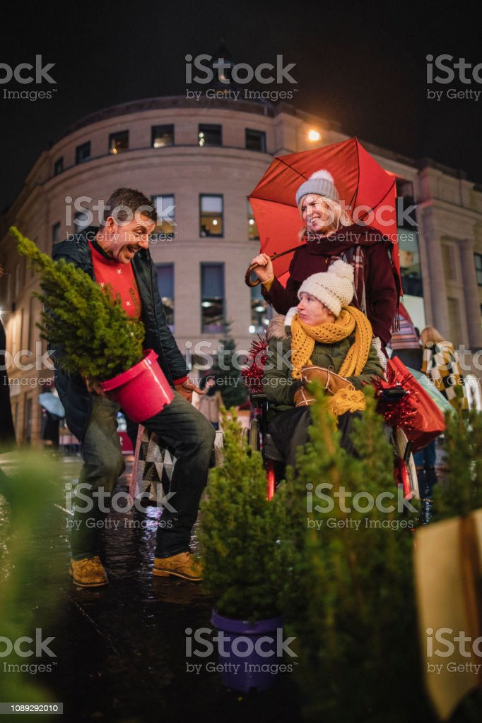 A front-view shot of a family buying gifts from a Christmas market...