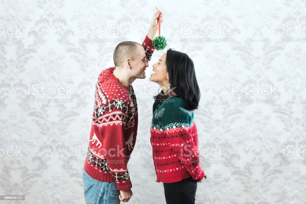 Christmas Sweater Couple Kiss Under Mistletoe Stock Photo & More ...