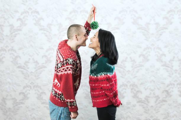 Christmas Sweater Couple Kiss Under Mistletoe stock photo