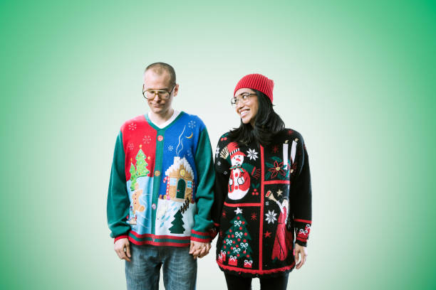Christmas Sweater Couple A man and woman wear ugly Christmas sweaters, the woman having fun and the man not enjoying it that much.  Horizontal image with green background. ugliness stock pictures, royalty-free photos & images