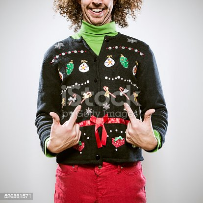 A man in a knit ugly Christmas cardigan button up sweater, complete with matching red pants and a green turtleneck.  He points proudly to his overly decorated sweater, a smile on his face.  Square crop.