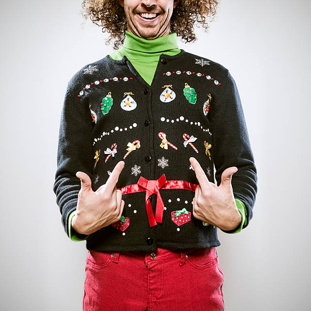 Christmas Sweater Man A man in a knit ugly Christmas cardigan button up sweater, complete with matching red pants and a green turtleneck.  He points proudly to his overly decorated sweater, a smile on his face.  Square crop. ugliness stock pictures, royalty-free photos & images