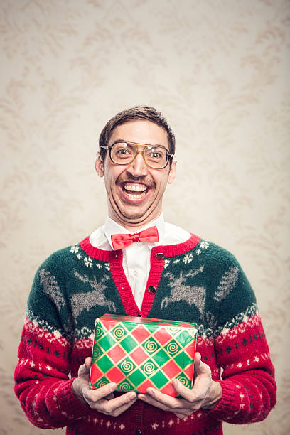 Christmas Sweater Nerd A man in a knit reindeer Christmas cardigan button up sweater, complete with matching red bow tie and a classy mustache shows off a wrapped gift he's ready to give as a present.  Damask style vintage wall paper in the background.  Vertical with copy space. cheesy grin stock pictures, royalty-free photos & images