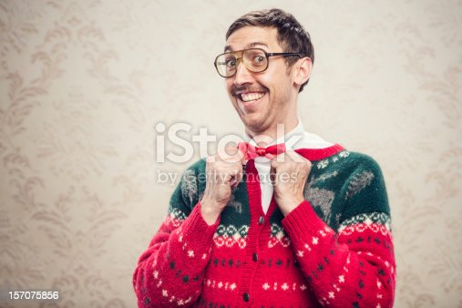 A man in a knit reindeer Christmas cardigan button up sweater, complete with matching red bow tie and a classy mustache.  He straightens his bow tie with a cheesy smile on his face, proud of his fashion style.  Damask style vintage wall paper in the background.  Horizontal with copy space.