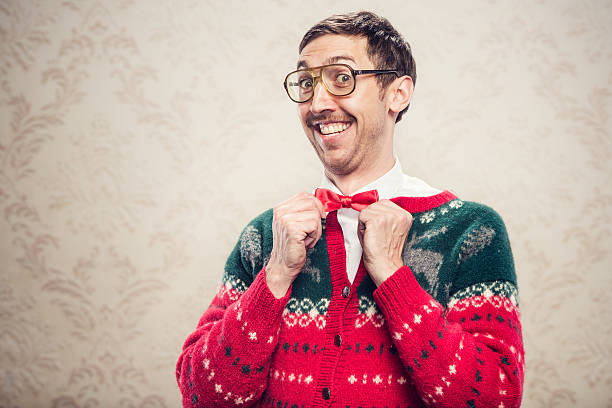 Christmas Sweater Nerd A man in a knit reindeer Christmas cardigan button up sweater, complete with matching red bow tie and a classy mustache.  He straightens his bow tie with a cheesy smile on his face, proud of his fashion style.  Damask style vintage wall paper in the background.  Horizontal with copy space. nerd stock pictures, royalty-free photos & images