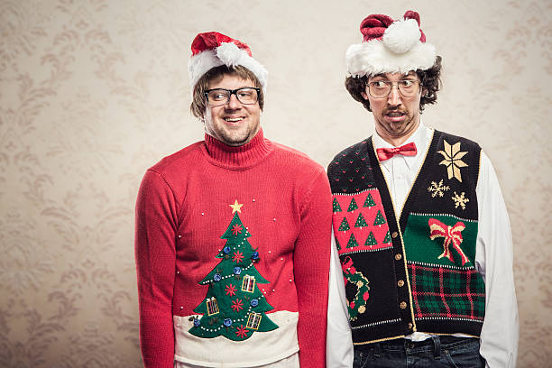 Christmas Sweater Nerds Two goofy looking men in ugly looking Christmas cardigans and sweaters (complete with matching red bow tie and a classy mustache) stand looking awkward for a holiday photo.  Damask style vintage wall paper in the background.  Horizontal with copy space. ugliness stock pictures, royalty-free photos & images