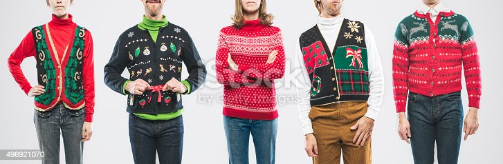 A panoramic image of a large group of people wearing knit ugly Christmas sweaters and cardigans with various bizarre patterns and decorations.  Horizontal on white studio background.