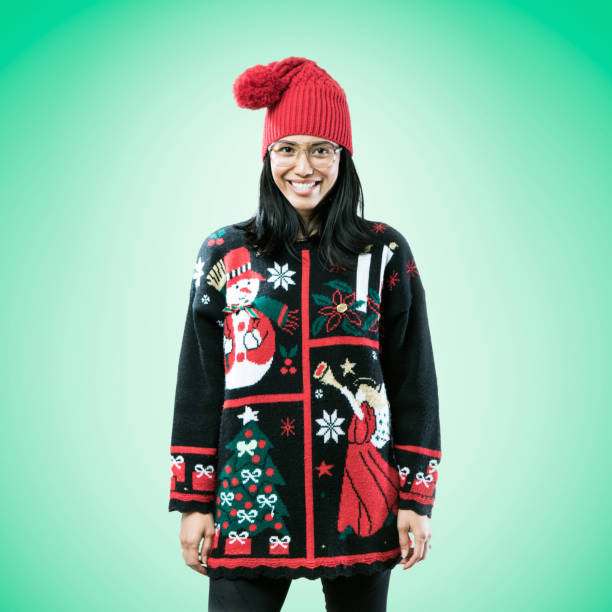 Christmas Sweater Woman on Green Background A happy Asian - Pacific Island woman wears an ugly Christmas sweater, having fun during the holiday season. ugliness stock pictures, royalty-free photos & images