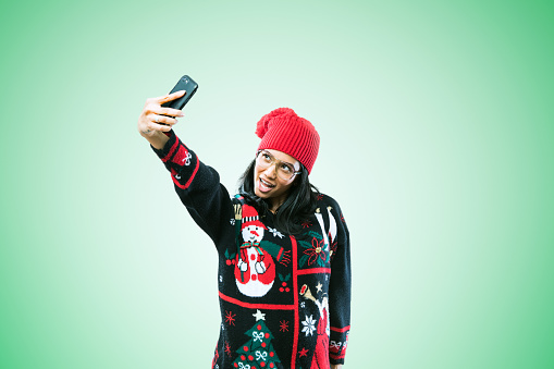 istock Christmas Sweater Woman Taking Selfie 886942288