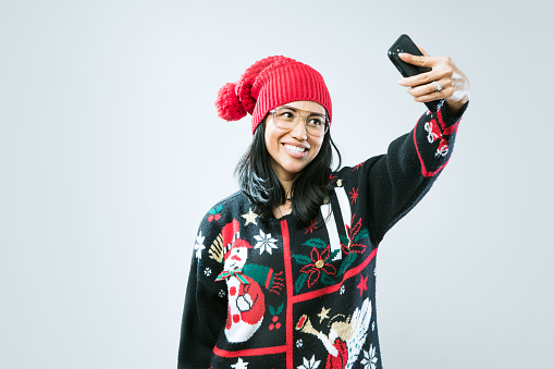 istock Christmas Sweater Woman Taking Selfie 886942430