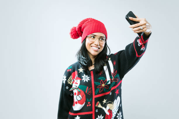 Christmas Sweater Woman Taking Selfie A happy Asian - Pacific Island woman wears an ugly Christmas sweater, having fun during the holiday season.  She takes a self portrait with her smart phone to share on social media. ugliness stock pictures, royalty-free photos & images