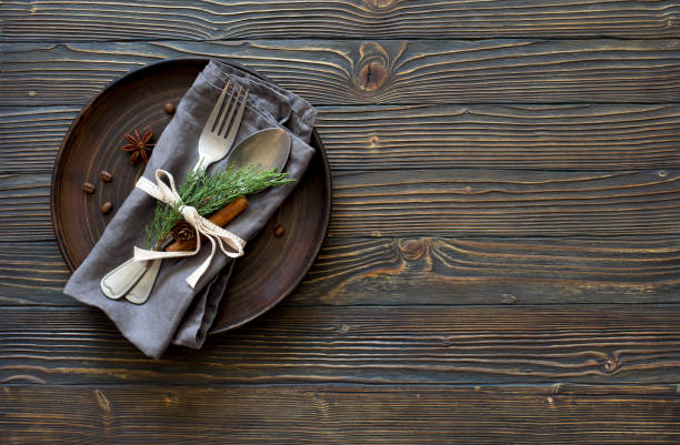 Christmas table place setting. Tableware with evergreen twigs, cone and spice stock photo