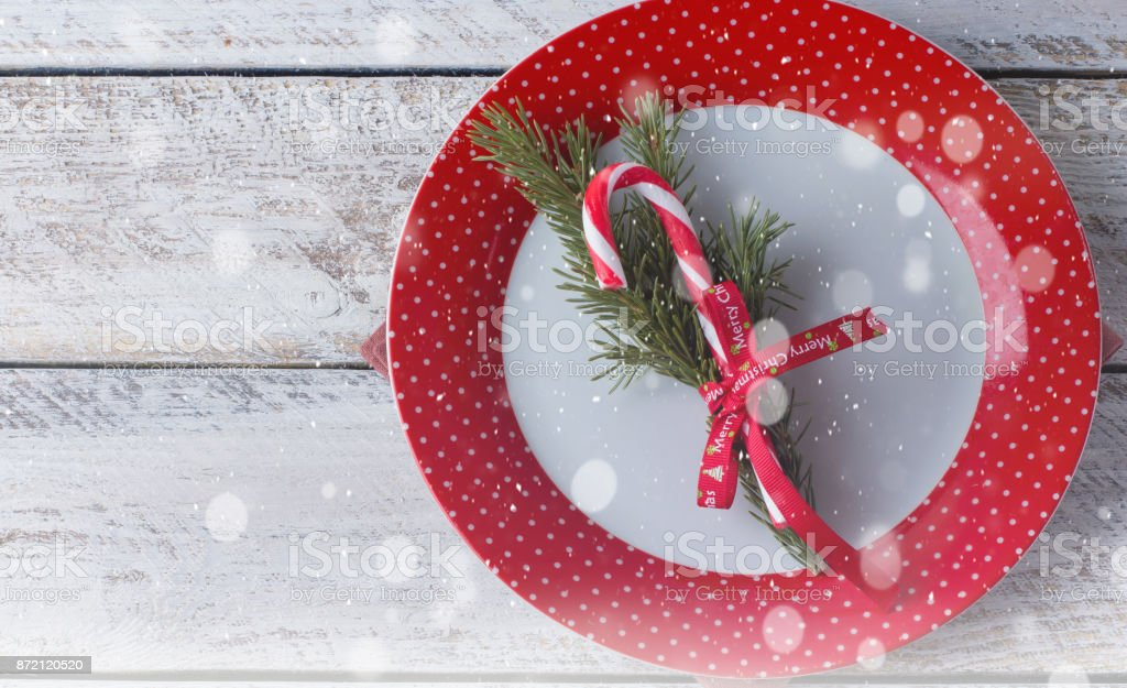 christmas table setting on white wooden table background with cutlery fir tree and candy cane