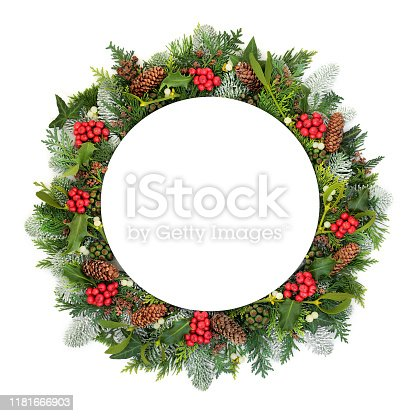Christmas table setting with round plate, holly and winter flora and fauna on whte background with copy space.