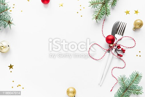 Christmas Table Setting with fir branch and red ornaments on white, flat lay, copy space. Christmas dinner, party design, concept - table setting with festive decoration.
