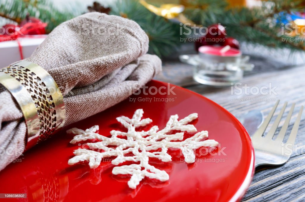 Christmas table setting. Red plate, fork, knife, candle, napkin,...