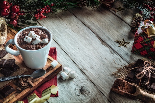 Christmas table setup with homemade chocolate mug with marshmallows with copy space on white rustic table