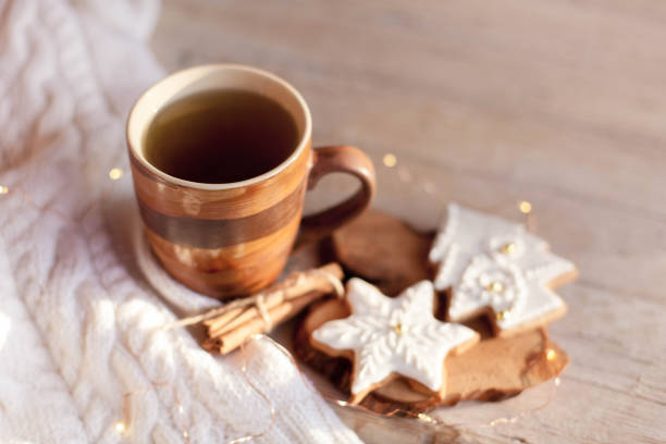 Christmas tea time. Mug of hot steamy beverage, gingerbread cookies at wooden and knitted background. stock photo