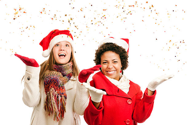 """Christmas Teenager Girls Wearing Santa Hats, Dazzled by Confetti Stars """"Subject: Horizontal half body view of two cute teenage girls dressed in festive Santa Claus hats and winter coats, gloves, and scarves, standing side by side. One girl is smiling for the camera, the other is looking up, dazzled by a swirling downpour of gold confetti stars they have tossed in the air. Shot against a white background."""" dazzled stock pictures, royalty-free photos & images"""
