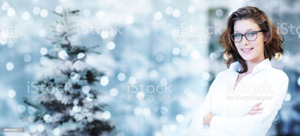 christmas theme, business smiling woman on blurred bright lights stock photo