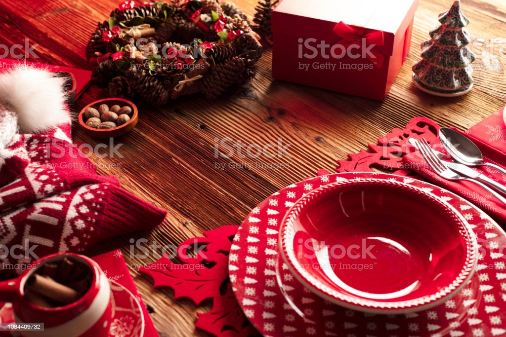 Christmas decorations, presents and tableware on wooden rustic table.